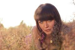 A menina bonita encontra-se em uma grama e em sonhos fotos de stock