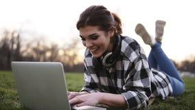 A menina bonita encontra-se na grama no parque Usa um portátil, conversando Fones de ouvido no pescoço Tem uma boa estadia dentro filme