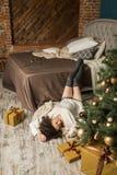 A menina bonita encontra-se pela cama ao lado da árvore no quarto Imagem de Stock
