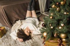 A menina bonita encontra-se pela cama ao lado da árvore no quarto Foto de Stock