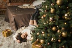 A menina bonita encontra-se pela cama ao lado da árvore no quarto Fotografia de Stock