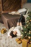 A menina bonita encontra-se pela cama ao lado da árvore no quarto Fotos de Stock Royalty Free