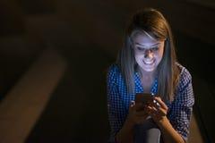 Menina bonita entusiasmado que recebe uma mensagem dos sms com boa notícia em um telefone celular fora Fotografia de Stock Royalty Free