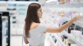 A menina bonita escolhe o perfume nos cosméticos compra, pulverizou-o no verificador, movimento lento video estoque