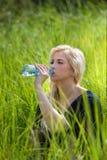 Menina bonita escondida na grama fresca que bebe a água saudável com minerais e microelementos Fotografia de Stock Royalty Free