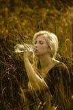 Menina bonita escondida na grama fresca que bebe a água saudável com minerais e microelementos Imagens de Stock