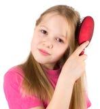 A menina bonita escova o cabelo Fotografia de Stock