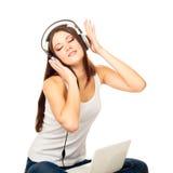 A menina bonita escuta a música através dos fones de ouvido Imagem de Stock