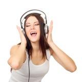 A menina bonita escuta a música através dos fones de ouvido foto de stock royalty free