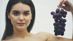 A menina bonita está comendo finamente frutos saudáveis Retrato de uma jovem mulher bonita que guarda um ramalhete maduro da uva  vídeos de arquivo