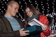 A menina bonita está dando seu presente do noivo na noite do inverno imagem de stock royalty free