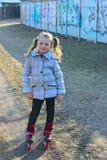 A menina bonita está em patins de rolo na terra Imagem de Stock Royalty Free