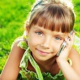 A menina bonita está falando em um telefone e está encontrando-se em um verde Imagem de Stock Royalty Free