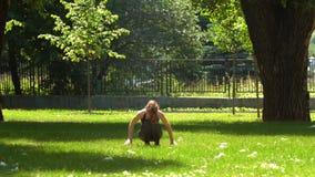 A menina bonita está fazendo a ioga no parque video estoque