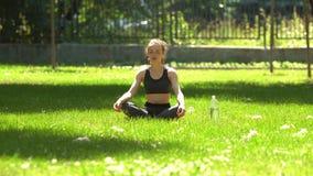 A menina bonita está fazendo a ioga no parque vídeos de arquivo