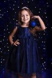 A menina bonita está guardando a bola azul do Natal imagens de stock