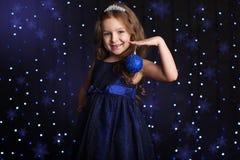 A menina bonita está guardando o brinquedo da árvore de Natal imagem de stock