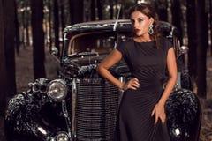 A menina bonita está na frente dos carros do vintage Fotos de Stock