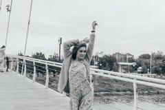 A menina bonita está na ponte, o vento funde em sua cara, desenvolvendo seu cabelo Sorrisos da menina foto preto e branco de danç fotos de stock