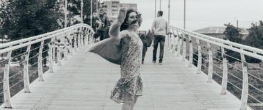A menina bonita está na ponte, o vento funde em sua cara, desenvolvendo seu cabelo Sorrisos da menina foto preto e branco de danç imagem de stock