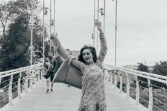 A menina bonita está na ponte, o vento funde em sua cara, desenvolvendo seu cabelo Sorrisos da menina foto preto e branco de danç fotografia de stock