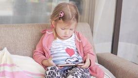 A menina bonita está olhando uns desenhos animados em um telefone celular video estoque