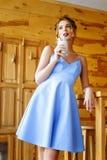 A menina bonita está perto de uma tabela de madeira alta e bebe o cappuccino fotos de stock royalty free
