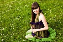 A menina bonita está sentando-se de pernas cruzadas na grama Fotos de Stock Royalty Free