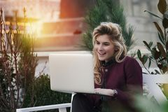 A menina bonita está sentando-se em um banco com um portátil em suas mãos em uma rua fresca com a cidade Um trabalho do concei fotos de stock