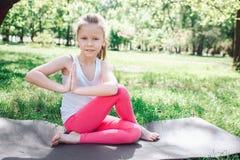 A menina bonita está sentando-se no carimate em uma pose da ioga Cruzou seus pés mas está mantendo suas mãos junto Fotografia de Stock