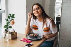 A menina bonita está tendo o almoço em um café em uma tabela de madeira foto de stock royalty free