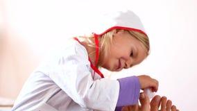 A menina bonita está tentando ser doutores Uma criança no terno de um doutor cura um pé a sua mãe filme