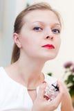A menina bonita está testando um perfume novo Fotografia de Stock Royalty Free