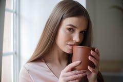 A menina bonita est? bebendo o caf? e est? sorrindo ao sentar-se no caf? imagens de stock