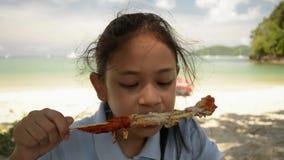 A menina bonita est? comendo a galinha grelhada na praia video estoque