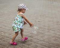 A menina bonita est? jogando com bolhas grandes na rua no dia de ver?o imagens de stock royalty free