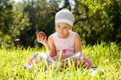 A menina bonita está lendo um livro fascinante Fotografia de Stock Royalty Free