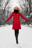 A menina bonita está saltando na neve Foto de Stock Royalty Free