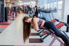 A menina bonita executa a hiperextensão em um banco no gym foto de stock royalty free