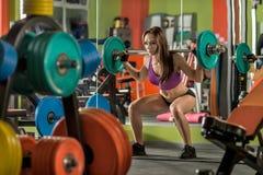 A menina bonita, executa o exercício squatting com peso Foto de Stock