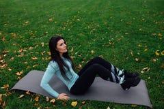A menina bonita faz exercícios com a imprensa na grama foto de stock