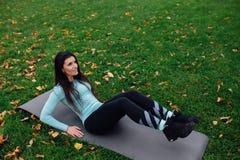 A menina bonita faz exercícios com a imprensa na grama imagem de stock royalty free
