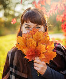 A menina bonita fecha a cara um ramalhete das folhas de bordo do outono Imagens de Stock