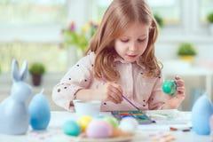 A menina bonita feliz da criança que tem o divertimento durante a pintura eggs para o leste foto de stock