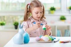 A menina bonita feliz da criança que tem o divertimento durante a pintura eggs para o leste fotografia de stock