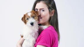 A menina bonita feliz em um t-shirt cor-de-rosa abra?a um cachorrinho Jack Russell Terrier, olha na c?mera, fundo cinzento, fim vídeos de arquivo