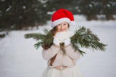Menina bonita feliz pequena na floresta do inverno imagens de stock