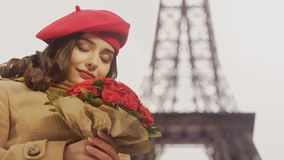 Menina bonita feliz que admira o ramalhete de rosas vermelhas no fundo da torre Eiffel video estoque