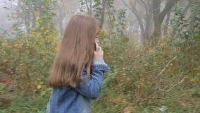 Menina bonita feliz que anda pela floresta e pelo telefone celular de fala video estoque