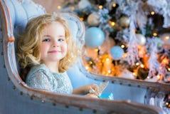 Menina bonita feliz que senta-se na cadeira e que guarda o presente de Natal Foto de Stock Royalty Free
